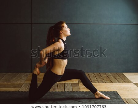 Redhead woman doing kneeling quad stretch Stock photo © sumners
