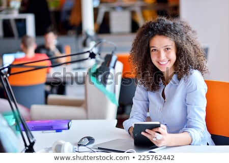 Beautiful young girl in the office is sitting at the desk and is holding glasses and a phone. Stock photo © Traimak