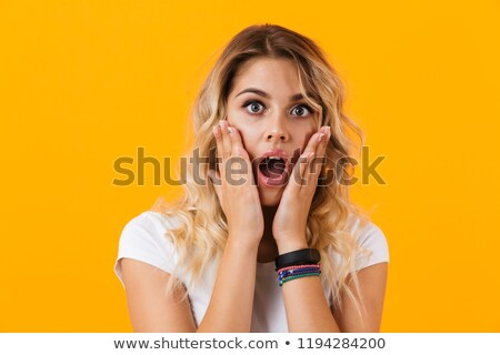 Photo of shocked woman in basic clothing screaming and touching  Stock photo © deandrobot