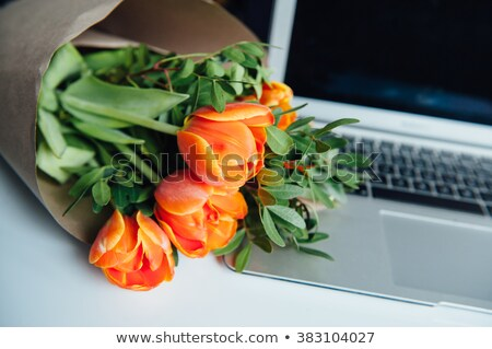 laptop on wooden floor with coffee tulips and notepad stock photo © elenabatkova
