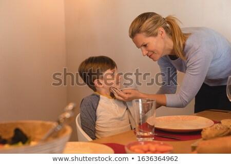 Vista lateral mãe boca guardanapo mesa de jantar casa Foto stock © wavebreak_media