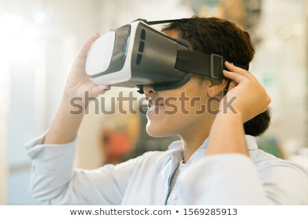 Young mixed-race woman taking on vr headset on head to watch presentation Stock photo © pressmaster