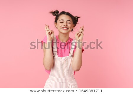 Photo of funny girl holding fingers crossed for good luck and smiling Stock photo © deandrobot