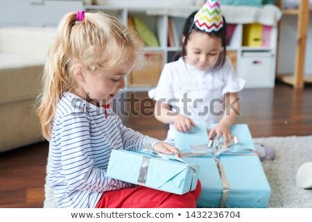 Cute blonde little girl unpacking her birthday gift Stock photo © pressmaster