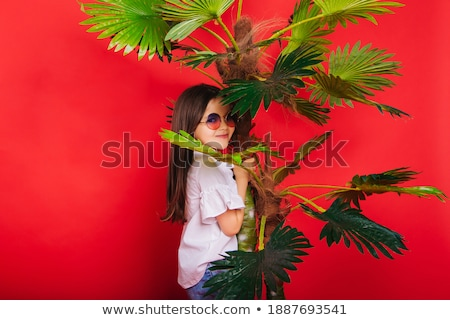 Adorable girl standing next to palm tree Stock photo © dash