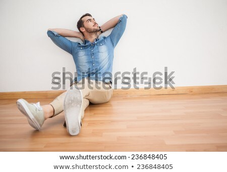 A handsome man sitting on the floor in the living room. Stock photo © justinb