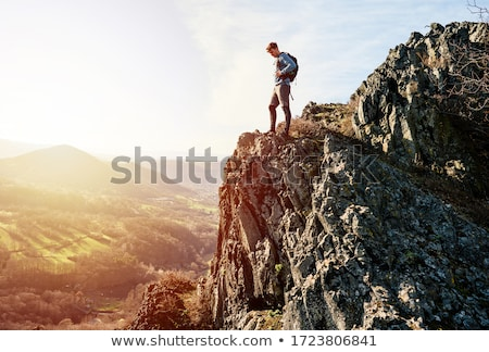 young caucasian man with backpack climbing the rock stock photo © master1305
