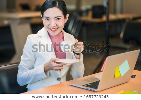 attractive relaxed young female using laptop and drinking coffee stock photo © deandrobot