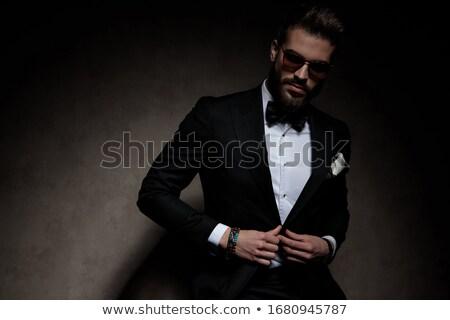 elegant guy posing seated in dark studio fixing his jacket Stock photo © feedough
