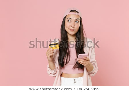 Pensive brunette woman in casual clothes holding smartphone Stock photo © deandrobot