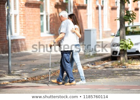 Woman Assisting Her Father While Crossing Road Stock photo © AndreyPopov