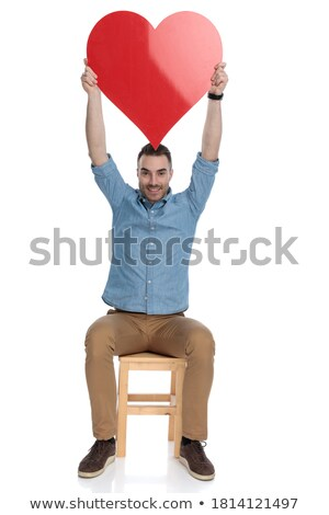 smiling young smart casual man sitting and holding a heart stock photo © feedough