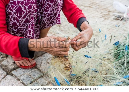 Hands of the old fisherman untangles fishing nets, Nha Trang Stock photo © galitskaya