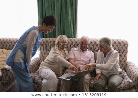 front view of female doctor laughing with senior people using laptop on sofa in living room at home stock photo © wavebreak_media