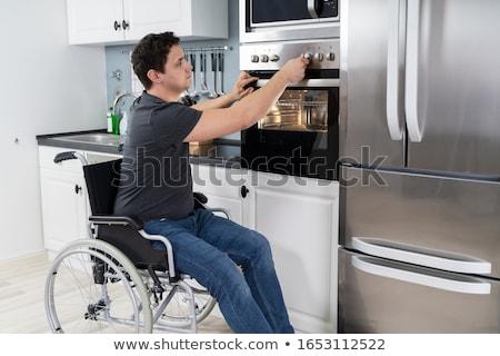 Disabili uomo forno a microonde forno cucina cottura Foto d'archivio © AndreyPopov