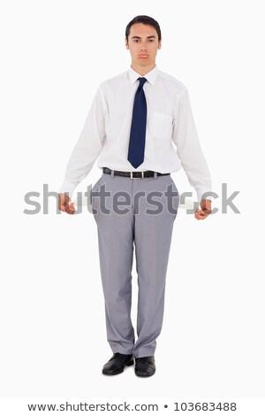 Upset man showing his empty pockets against white background Stock photo © wavebreak_media