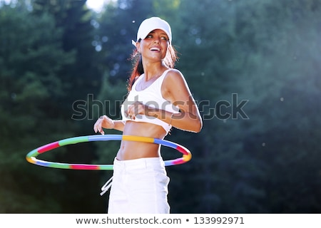Woman rotates hula hoop on nature background Stock photo © HASLOO