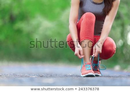 woman ties laces on green shoes Stock photo © ssuaphoto