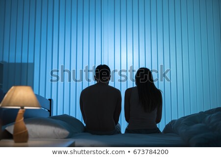 man sitting on the bed with two women on the back Stock photo © dolgachov