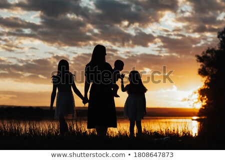 Happy family with little girl standing on beach in evening, stan stock photo © Paha_L