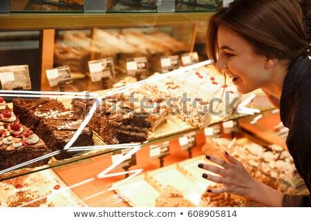 Happy young woman standing in supermarket choosing sweeties Stock photo © deandrobot