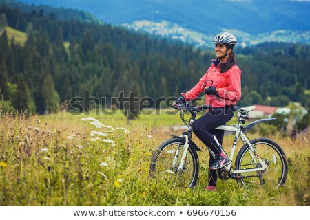 Woman cyclist relaxing in field Stock photo © IS2