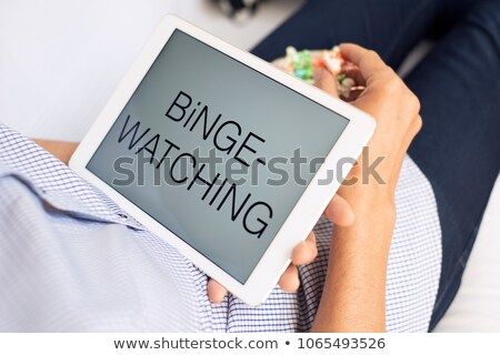 man and tablet, with the text binge-watching in it