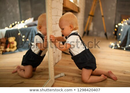 baby boy plays near the mirror against background of glowing lig stock photo © stasia04