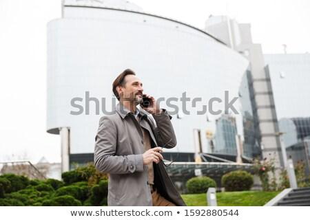 Image of satisfied businessman in stylish formal wear, walking t Stock photo © deandrobot