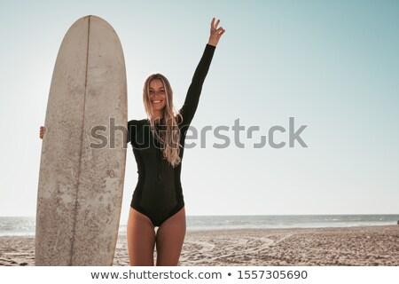 Feminino surfista em pé prancha de surfe praia Foto stock © wavebreak_media