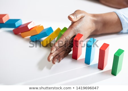 Businessperson's Finger Stopping Dominoes From Falling Stock photo © AndreyPopov