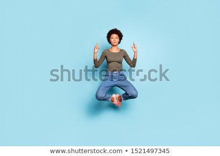 A girl sitting in yoga asana on a blue background. Stock photo © Illia