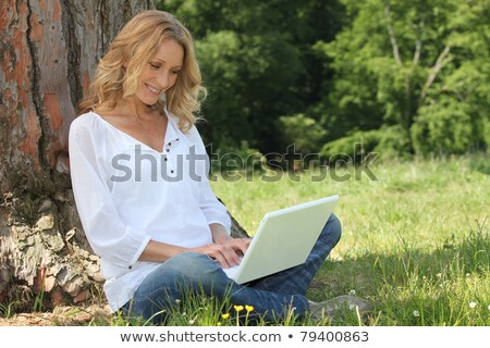 Blond woman sat by tree with laptop Stock photo © photography33