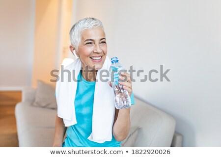 Mujer agua potable botella toalla alrededor cuello Foto stock © deandrobot