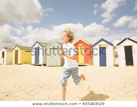 Boy running in front of beach huts Stock photo © IS2