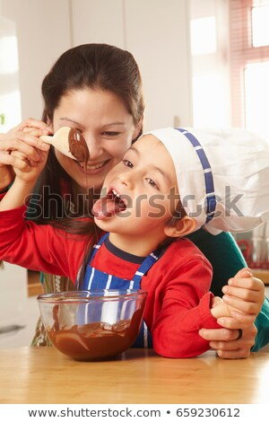 Boy licking chocolate off spoon with mum Stock photo © IS2