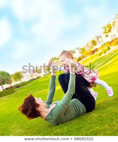 mother lying on grass holding up baby stock photo © is2