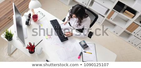 a young girl sits in the office holds a pen in her hand and looks through documents stock photo © traimak