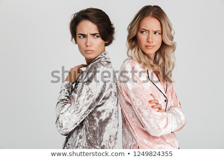 Two upset girls wearing pajamas isolated over gray Stock photo © deandrobot
