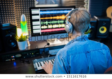 Rear view of young man in headphones making music by computer monitor Stock photo © pressmaster
