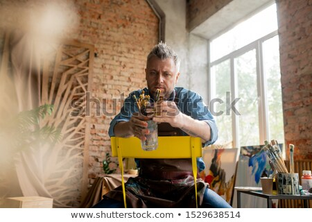 Contemporary mid-aged artist sitting on chair in studio and choosing paintbrush Stock photo © pressmaster