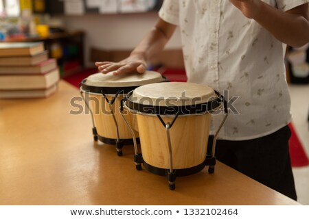 Mid section of cute mixed-race schoolboy playing bongo in a classroom at elementary school Stock photo © wavebreak_media
