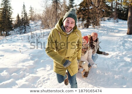 Happy young man in winterwear pulling sledges with cheerful girl in park Stock photo © pressmaster