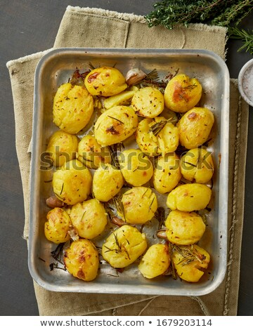 Oven baked whole potatoes with seasoning and herbs in metalic tr Stock photo © dash