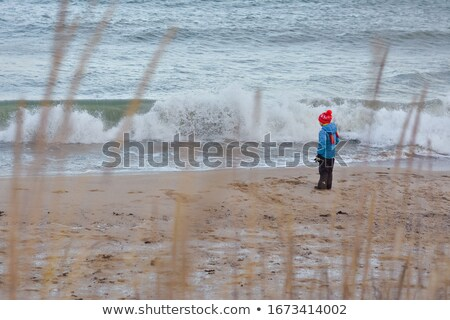 Boy watching the ocean on a stormy, windy day Stock photo © lovleah