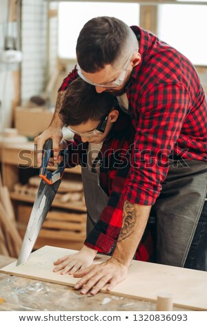 craftsman holding two wooden boards and a saw Stock photo © photography33
