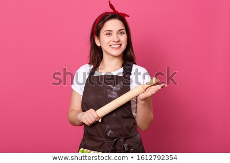 Happy female chef in unifrom holding rolling pin Stock photo © wavebreak_media