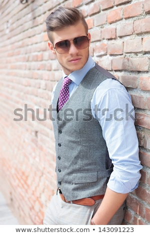 man with his hands in pocket, leaning on a wall Stock photo © feedough