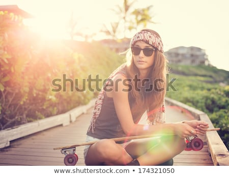 Beautiful young woman with skateboard, backlit at sunset Stock photo © vlad_star