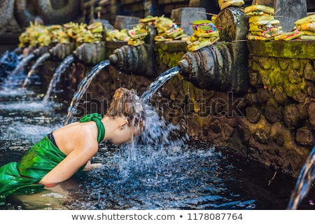 Foto stock: Woman In Holy Spring Water Temple In Bali The Temple Compound Consists Of A Petirtaan Or Bathing St